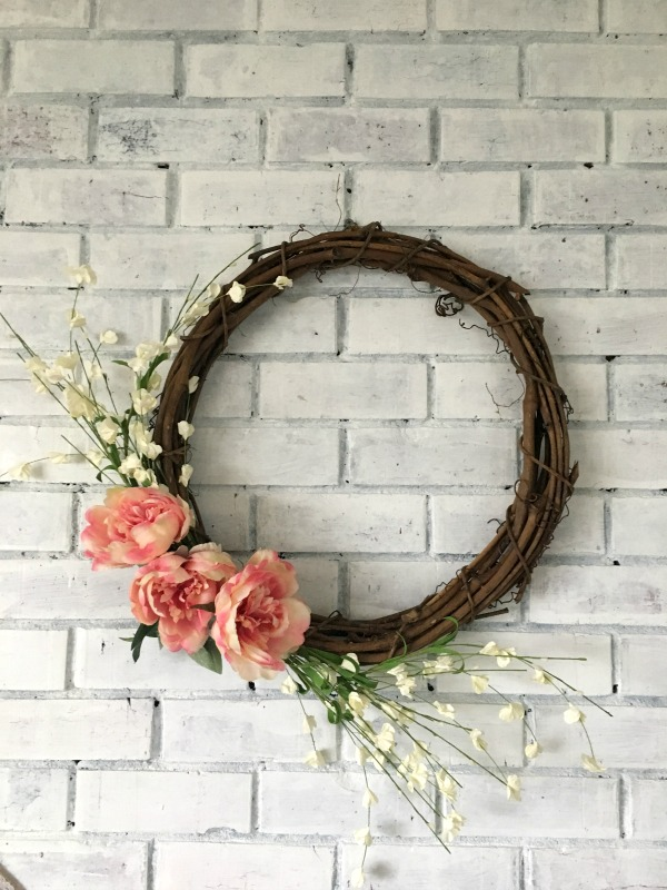 A grapevine wreath with pink and white flowers offset on a whitewashed fireplace