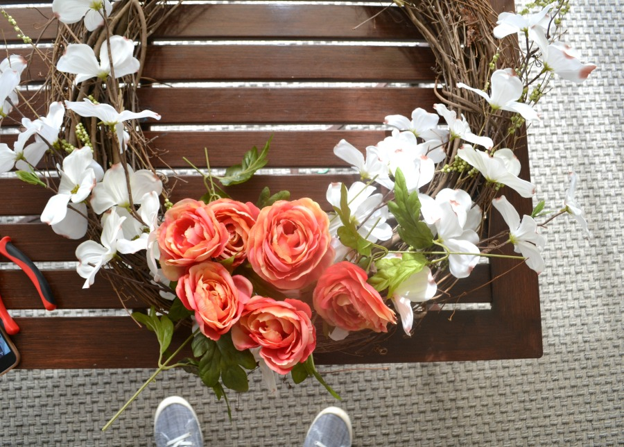 Faux flowers sitting on a grapevine wreath on an outdoor coffee table