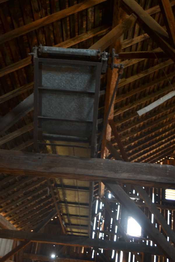A view up in the barn of an old hay elevator sitting in the rafters