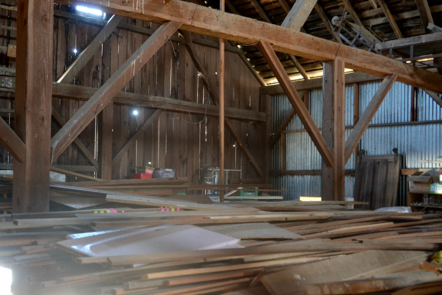 A view in a barn loft of a completely covered floor of wood of all shapes and sizes
