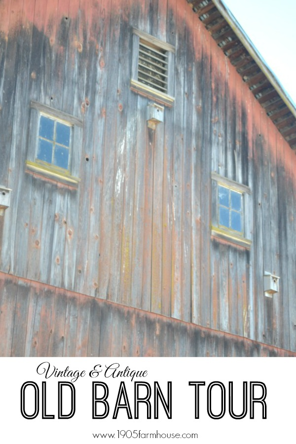 The outside of an old barn that is faded red with two top windows with text overlay that states old barn tour