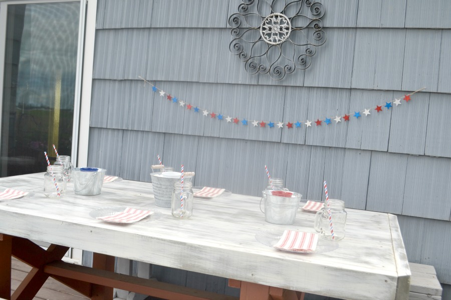 A side view of an outdoor table against a house with three metal buckets on the table with candles inside and plates and napkins and each seat with a blue house siding in the background