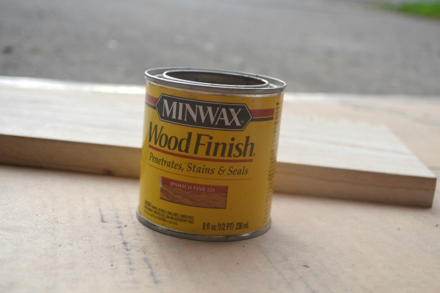 A small can of Minwax stain in front of a board on a piece of cardboard