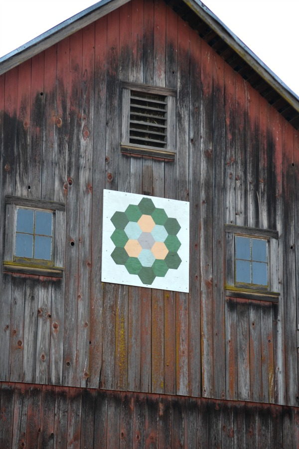 A flowered quilt square with a white background on a fading red barn