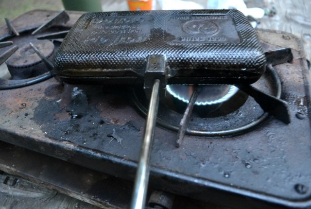 A closed double pie iron being cooked over a propane burning stove