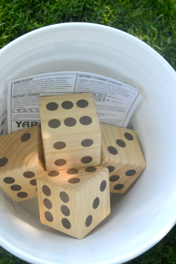 An above view of inside a bucket with wood dice and a scorecard