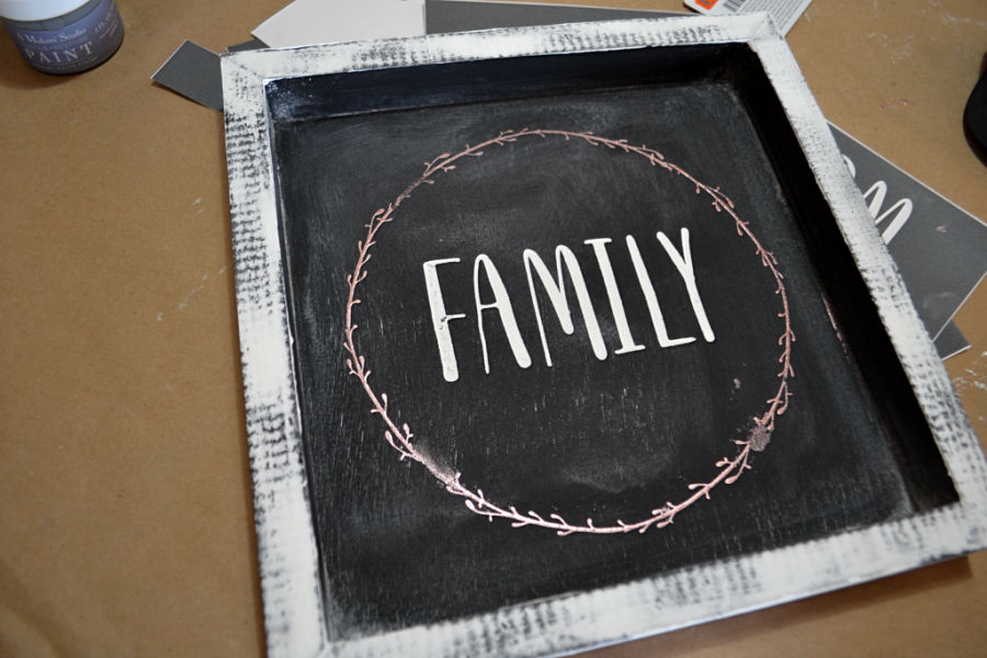 An above view of a black sign with a white border and the word family in the middle of a copper leaf design