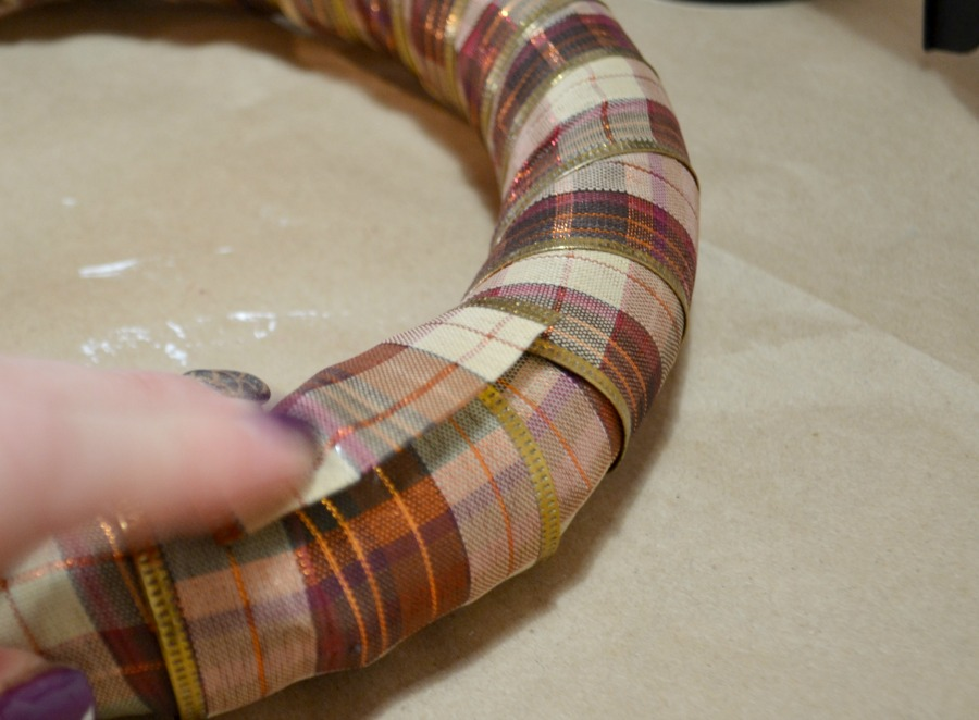 Fall plaid ribbon wrapped around a foam ring, a close up of fingers pushing down the ribbon end onto the ring