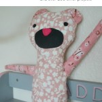 A pink flowered handmade teddy bear sitting on a light purple shelf would make a good beginner craft project