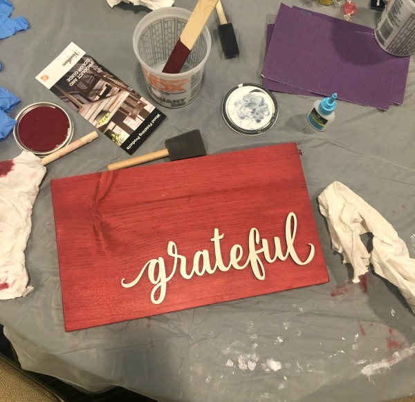 A red sign with a wood cutout of grateful attached surrounded by paint brushes, rags and stirring sticks