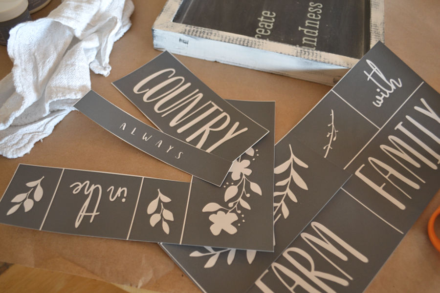 A scattered pile of mesh stencils on an oak table with a white edged sign in the background