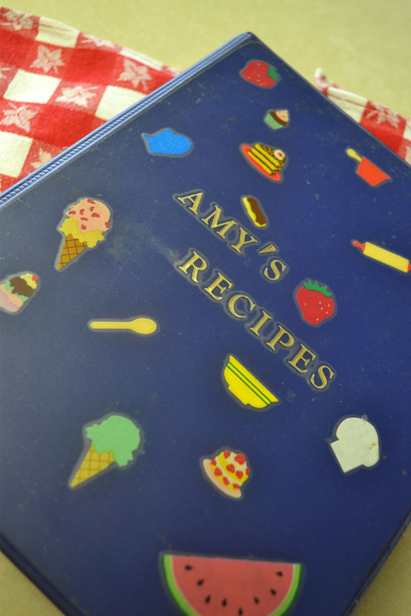 """A blue binder covered with food stickers with the words """"Amy's Recipes"""""""