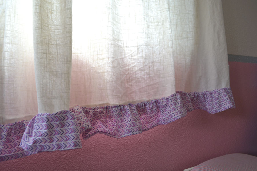 A close up of pink and purple fabric ruffles at the bottom of a linen curtain with a pink wall behind it