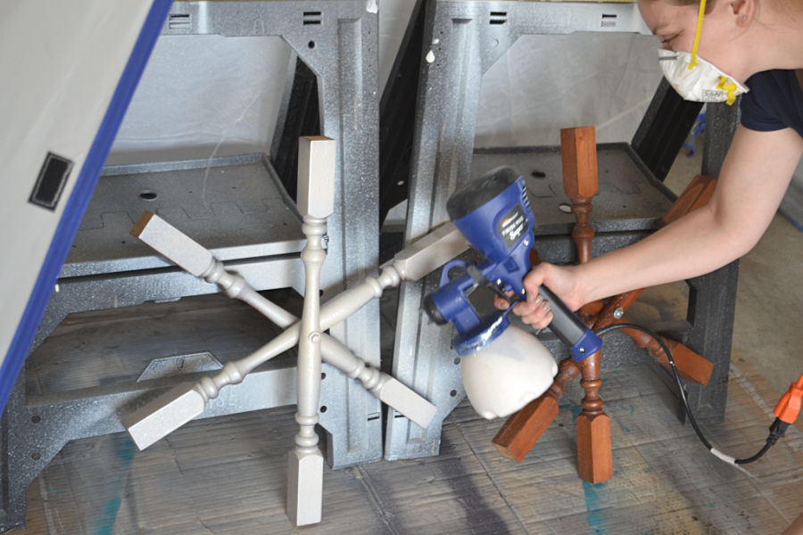 A shimmery ivory painted staircase spindle snowflake being painted with a paint sprayer