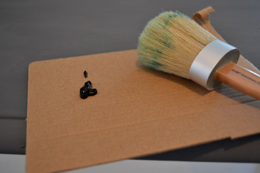 A piece of cardboad with a small amount of dark brown wax with a brush for applying wax