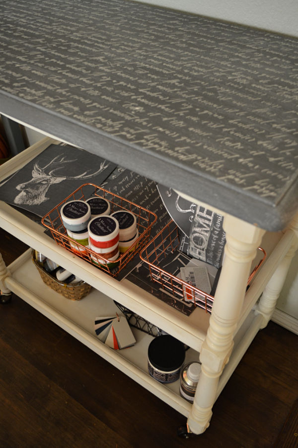 An above side view of the finished cart with paint supplies and stencils on each shelf and the French scripting on top