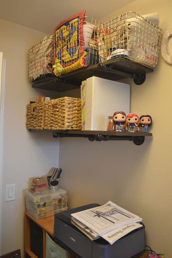 A side view of pipe shelving on wall with baskets on each shelf with a cube organizer below with a printer on top
