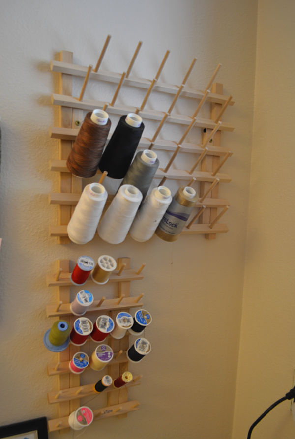 A close up of two different sized wood thread dowel holders attached to the wall with different colors of thread