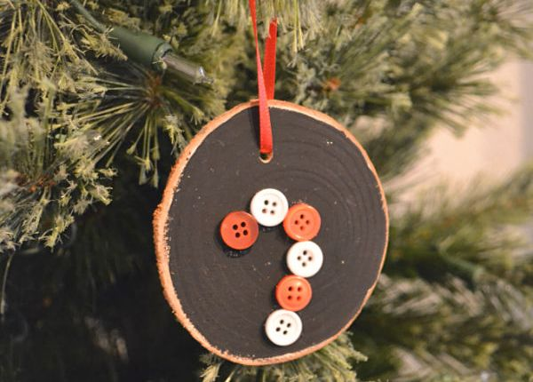 A green tree with a black painted wood slice hanging by a red ribbon with a red and white candy cane in buttons