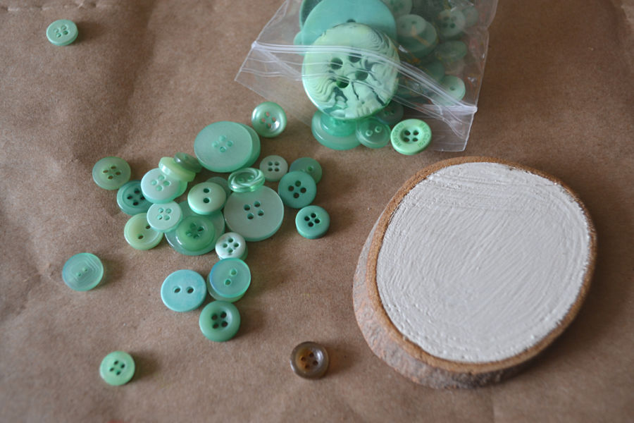 Brown craft paper with a wood slice painted in white and green buttons spilled next to the wood slice