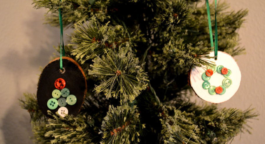 A green Christmas tree with 2 wood slice ornaments hanging by green ribbon, one ornament is painted back with a button tree, the other is white with a button wreath