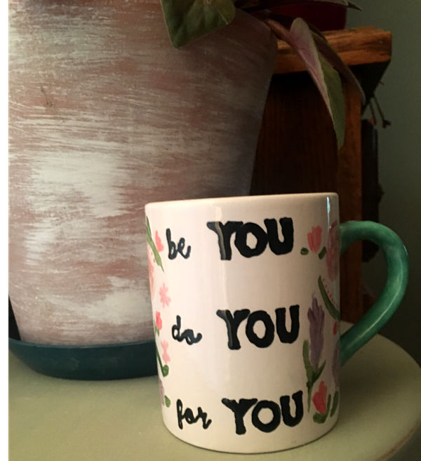 "A completed fired and hand-painted mug with the words in black ""be you, do you, for you"""
