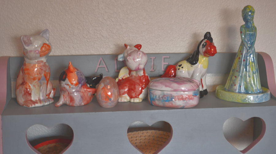 A collection of ceramic animals in assorted colors painted by a child on a shelf