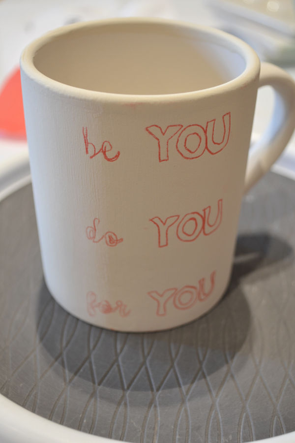 "A white mug on a gray plate with red traced letters ""be you, do you, for you"""