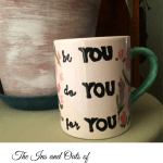 "A painted and glazed white mug with a green handle with the words ""be you, do you, for you"" painted on the side in black"