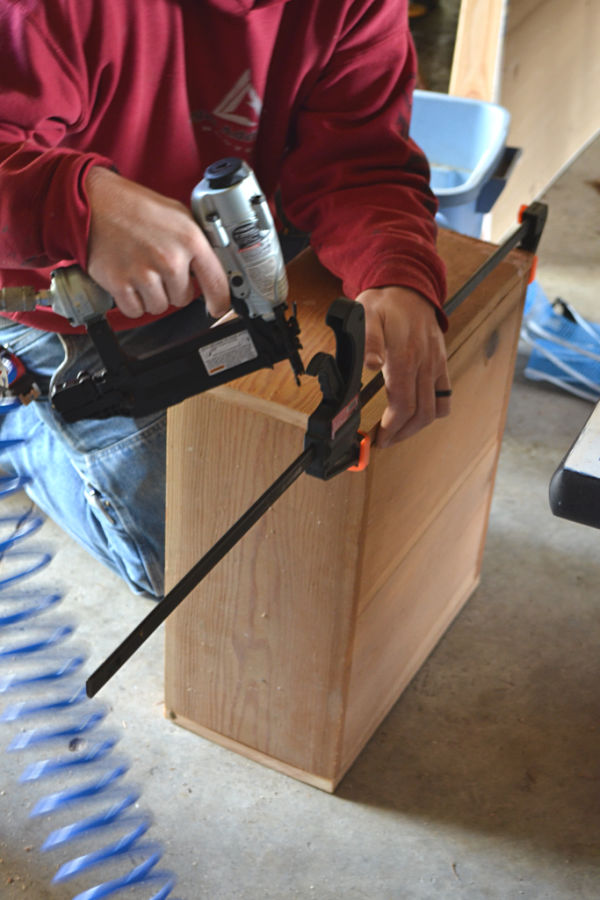 A wooden box with a c-clamp being used whie a brad nail gun nails the final side on the box