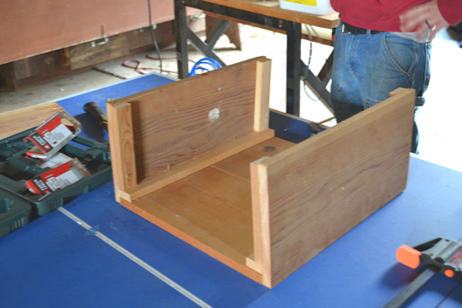 A wooden box with two sides built with bracing on a blue table