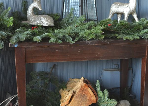A small brown bench hold fresh evergren boughs, firewood is piled below with a white sign that says let it snow