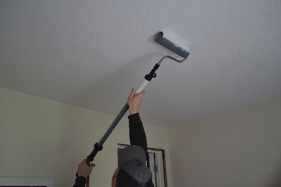 A man with a hat holding a paint stick roller and painting a ceiling white