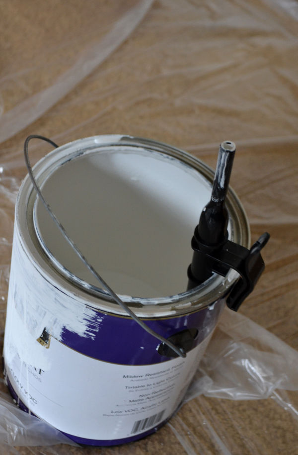 A can of white paint sitting on plastic on a floor with a black tube attached to the side