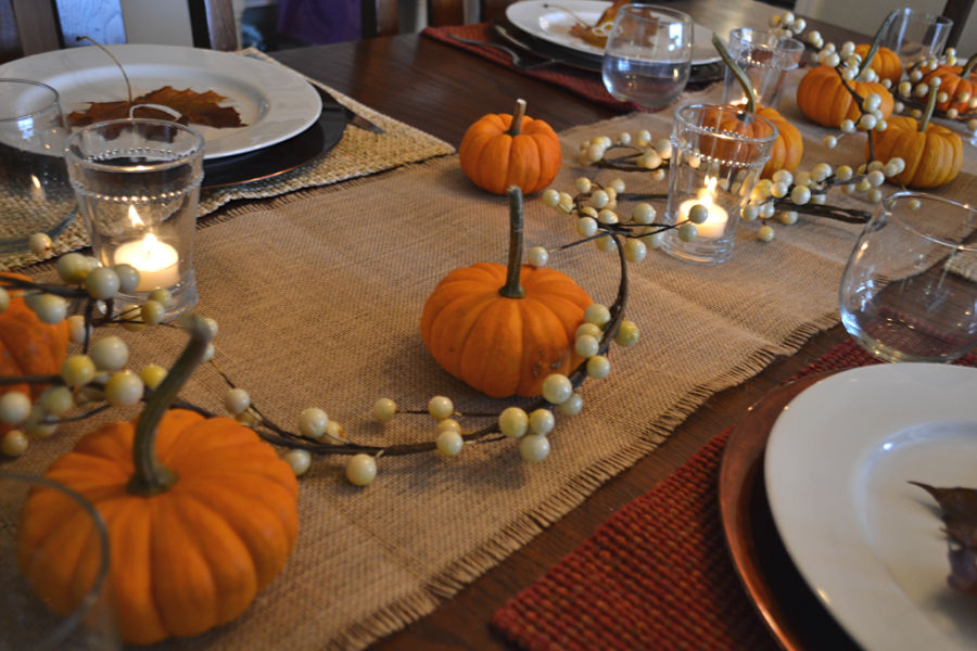 A close up picture of a burlap table runner with small orange pumpkins, white berry garland and candles lit in a glass