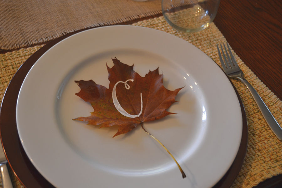 A white plate sitting on a woven placemat with a maple leaf with the letter C in white on top of the plate