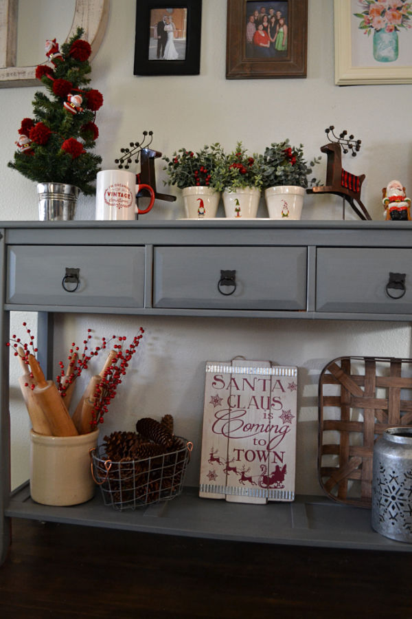 A console table with reindeer and a tree on top and a crock with rolling pins and pine cones in a basket and a sign below