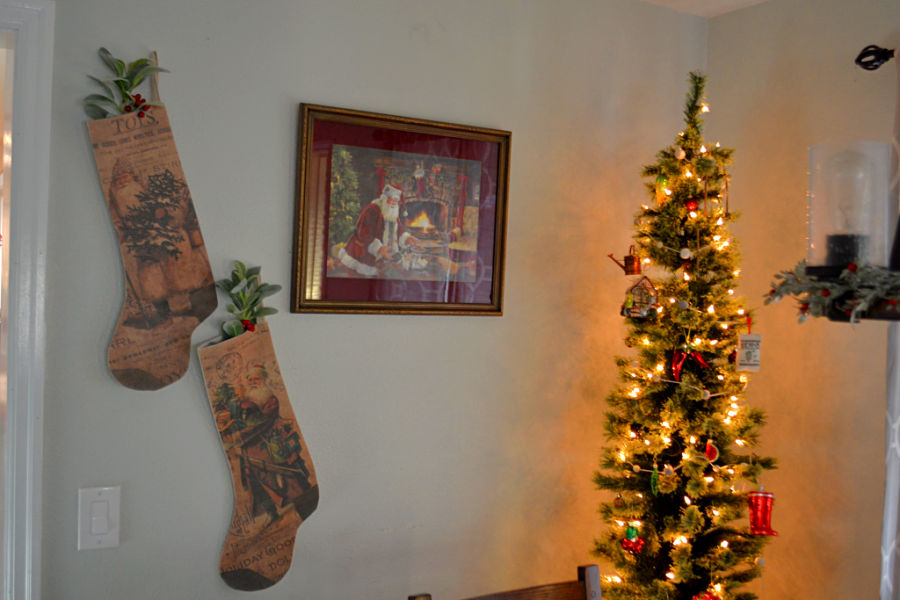 A pencil tree lit up on the right with a framed Santa photo hung on the wall with vintage grain sack stockings to the left of the picture