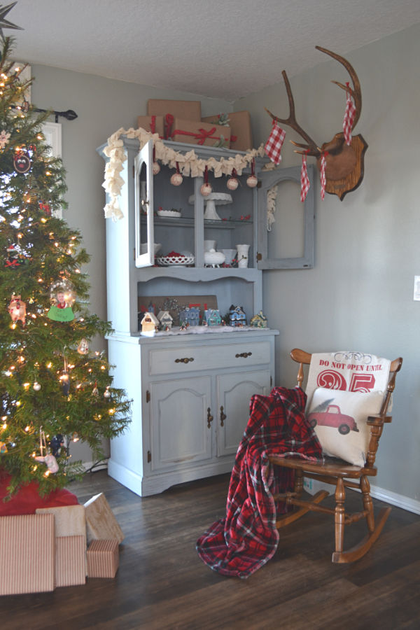 A blue grey hutch displaying a whtie milk glass collection with red and green accents and a Christmas tree to the left of the hutch