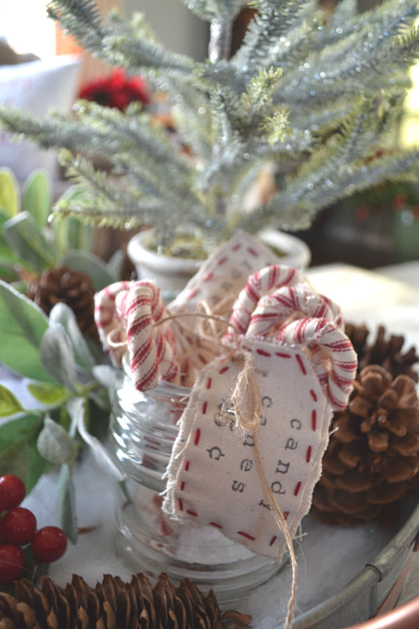 Fabric wrapped candy canes displayed in a vintage light cover with greenery in the background