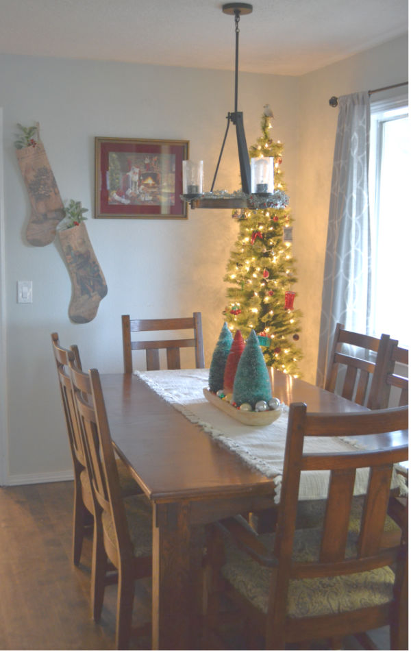 A thin pencil tree in the corner of a dining room with open window shades on the right, a dining room table with a table runn and bottle trees in the center and stockings hanging on the wall next to a picture of Santa