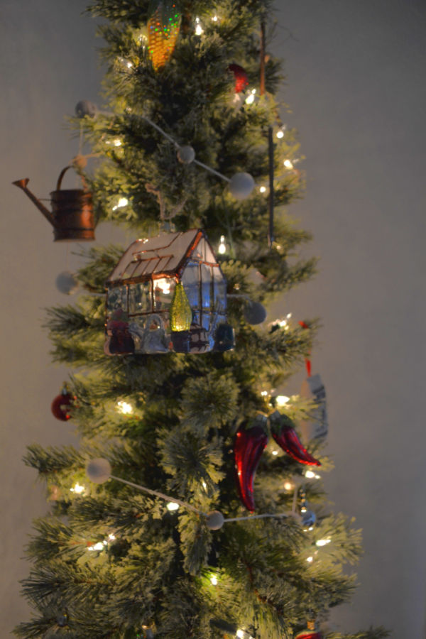 A close up of a pencil tree with a glass greenhouse ornament, a watering can, peppers and felt ball garland