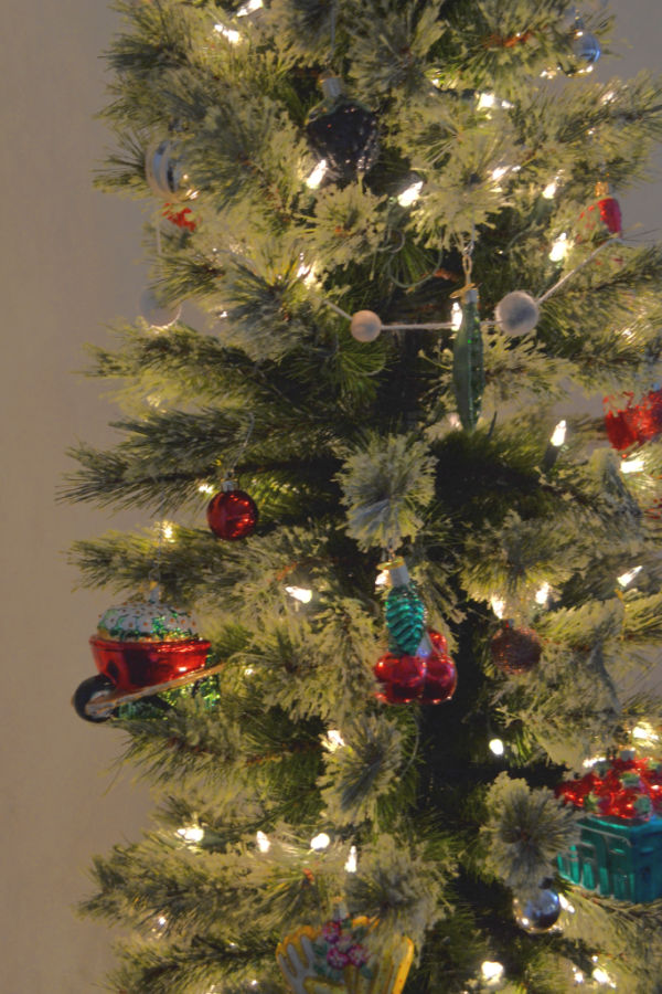 A pencil tree with a red shiny wheelbarrow glass ornament on the left and red cherries in the center