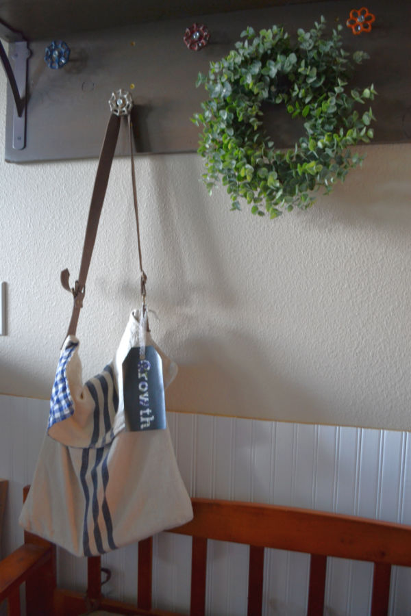 """A linen bag being hung from a hook with a faux leather bag tag that says """"growth"""""""
