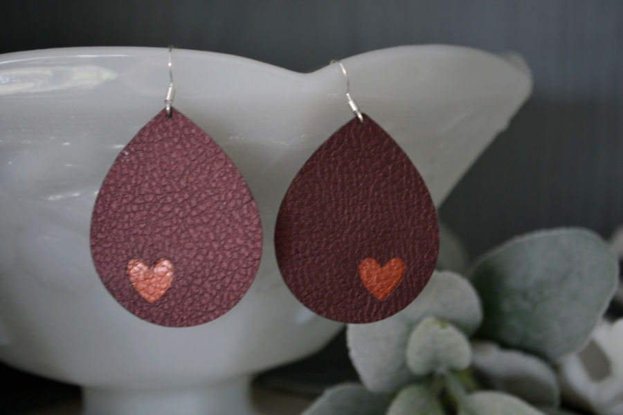 Finished deep purple tinted faux leather teardrop earrings with copper colored faux leather heart cutouts hanging from a milk glass bowl