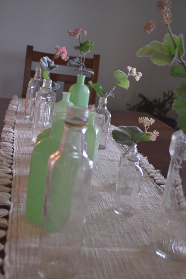 A close up view of a white table runner with clear and green glass bottles lined down the table runner with faux greenery tucked into some of the bottles