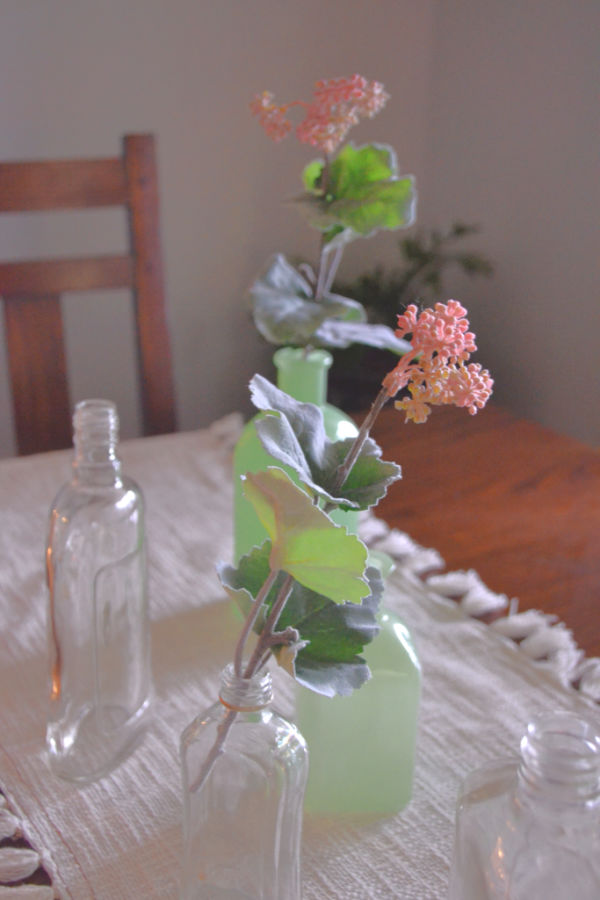 A close up of faux coral bell flower greenery in a vintage clear glass bottle on a white table runner on a dark wood dining room table