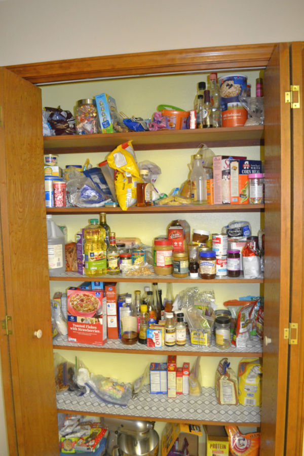 A view of 2 accordian doors opened to a 5 shelf pantry with yellow walls and food bags and bottles spread haphazardly over every shelf