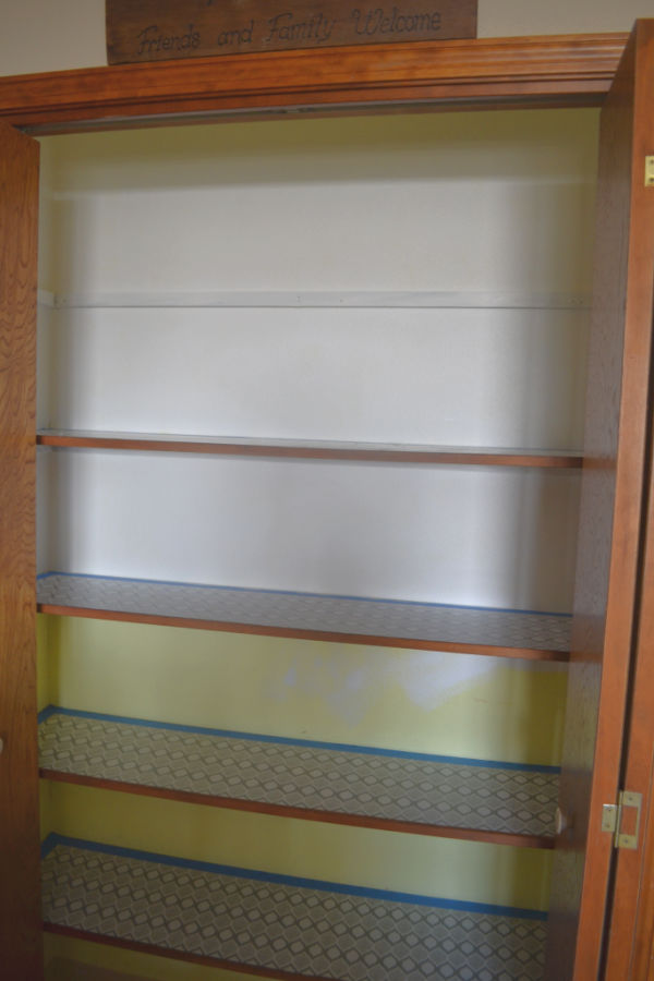 Accordian doors opened up to reveal 5 shelves ina pantry with unpainted yellow walls