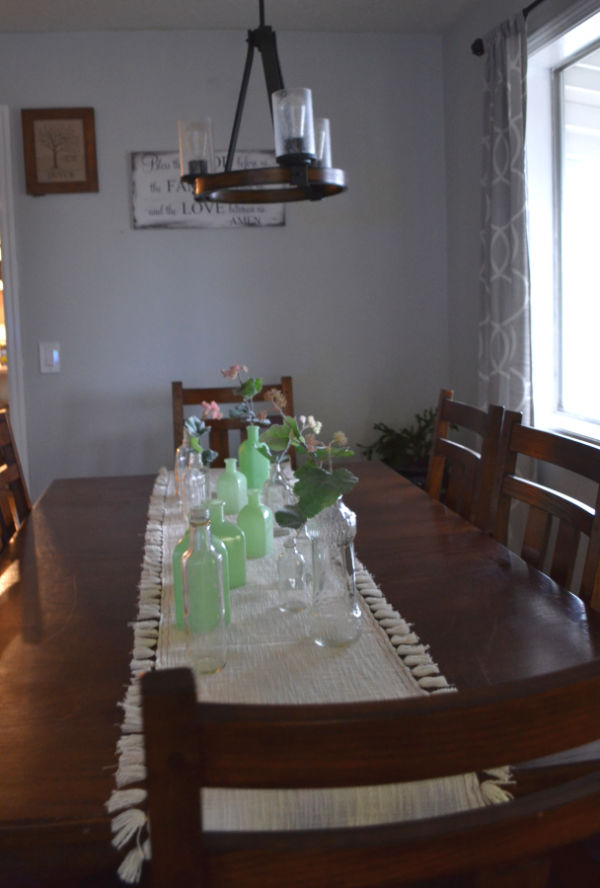 A long view down a dark brown dining room table with milk glass green vases and vintage bottles on white table runner